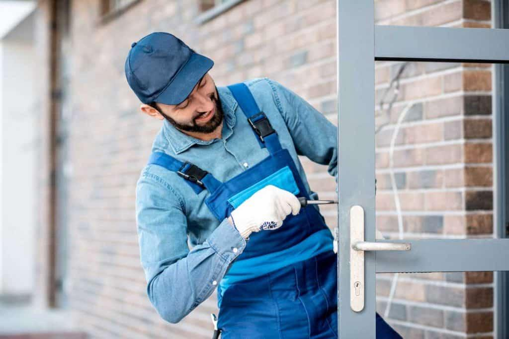 Builder in uniform installing a door lock into the entrance door of a new house